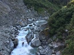 Roaring river passing under a bridge