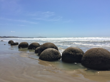 The boulders all lined up on the beach.