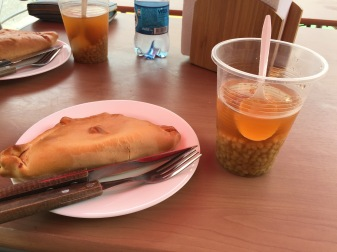 "Another empanada, along with some ""mote con huesillo"", a non-alcoholic sweet drink with a dried peach and wheat in it."